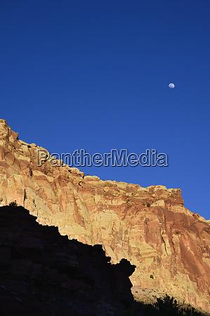 moon over cliff in shadow in