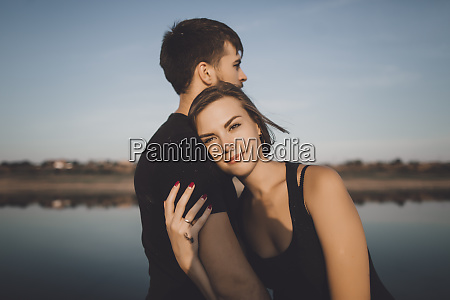 young couple embracing by lake