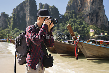young man photographing on beach in