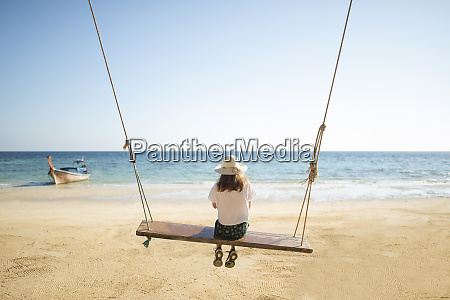 young woman on swing at beach