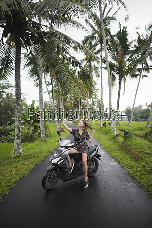 young woman taking selfie on motorcycling