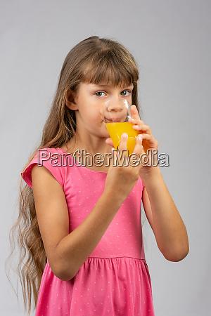 the girl drinks orange juice from