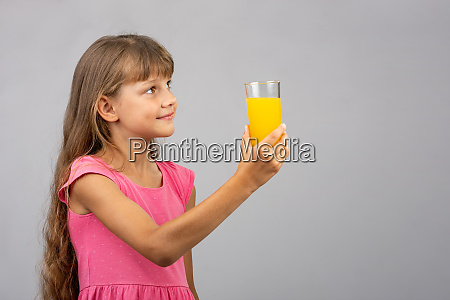 a girl holds a glass of