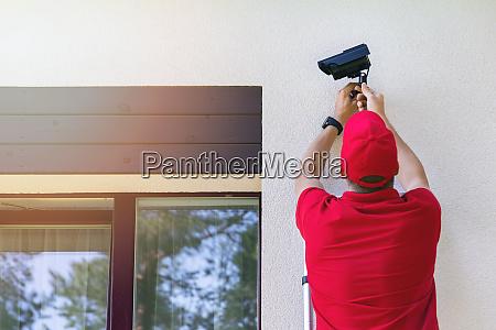 technician installing outdoor security surveillance camera
