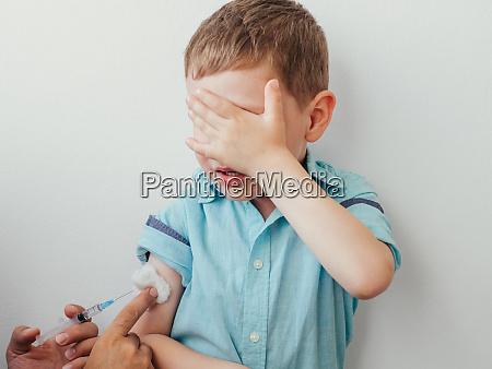 kleiner junge hat angst zu impfen