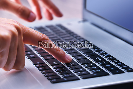 haendeeingabe auf einer laptop computertastatur