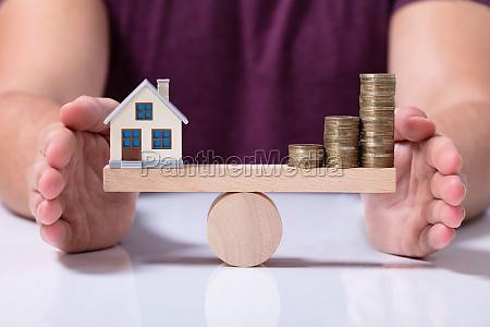 haus modell und geldmuenzen balancieren auf