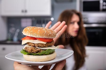 frau lehnt ungesundes essen ab