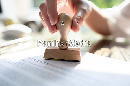 female hands stamping document in office