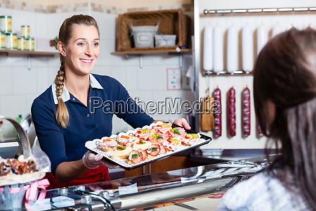 verkaeuferin in metzgerei bietet fingerfood an