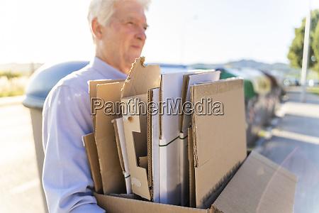 senior mann recycling karton tragen karton