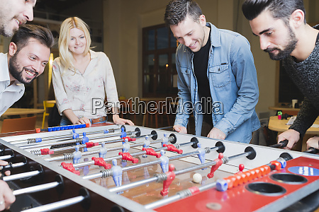 happy colleagues playing foosball in office