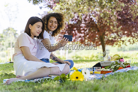 two happy women with cell phone