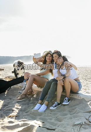 happy female friends with dog taking