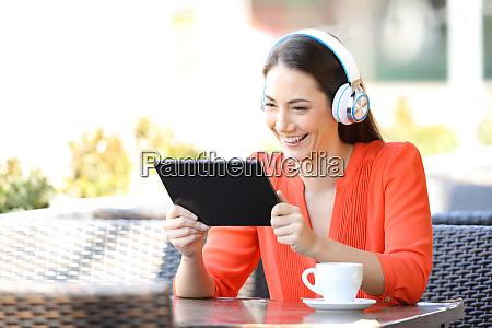 glueckliche weibliche beobachten medieninhalte auf tablet