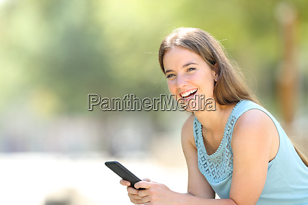 happy woman holding phone laughs looking