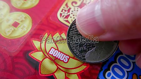 nahaufnahme der frau kratzen lottoschein