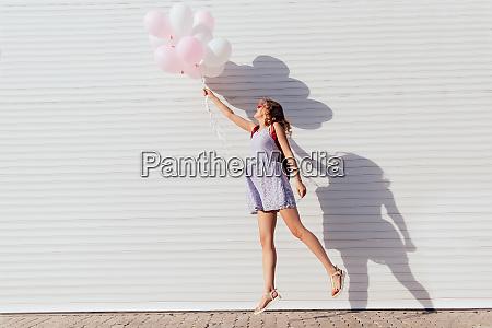 seitenansicht des springenden maedchens mit luftballons