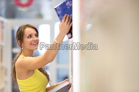 huebscher student in einer bibliothek flaches