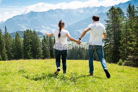 couple running on field in mountains
