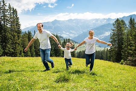 familie mit tochter laeuft auf feld