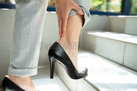 geschaeftsfrau hand beruehren ihren schmerzenden knoechel