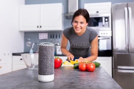 frau, die, musik, auf, wireless-lautsprecher, hört - 27137518