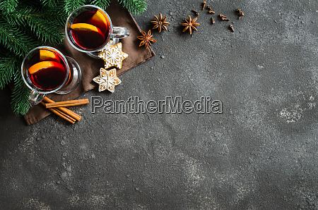 weihnachtsgluehwein mit gewuerzen auf dunklem hintergrund