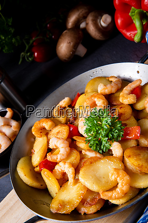 eine leckere bratkartoffel und garnelenpfanne