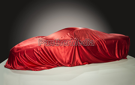 sports car under an red drape