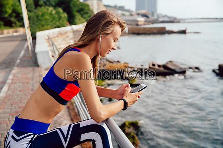 sportlerin in kopfhoerern mit dem smartphone