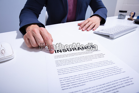 businessman showing insurance document over white