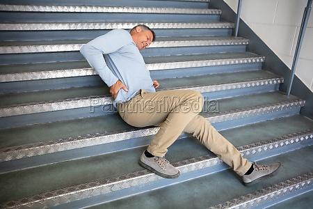 reifer mann liegt auf treppe