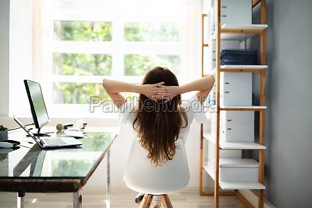 entspannte geschaeftsfrau sitzt im buero