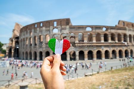 frau haelt herz geformte italienische flagge