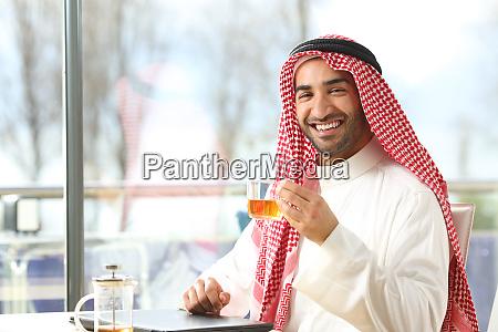 gluecklicher arabischer mann haelt eine tasse