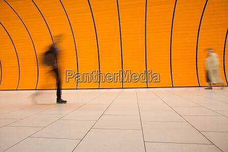 people rushing through a subway corridor