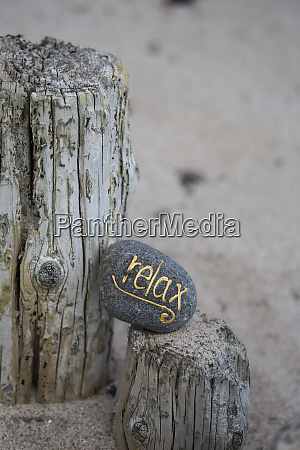 relax lettering on pebble on sandy