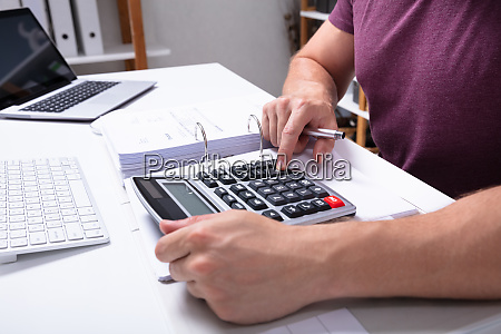 male businesspersons hand using calculator over