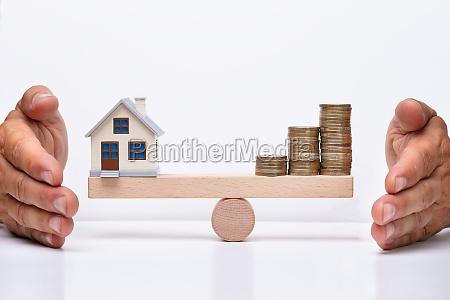 modell haus und muenzen balancieren auf