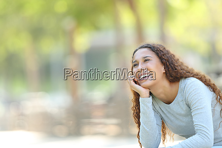 happy mixed race woman dreaming in