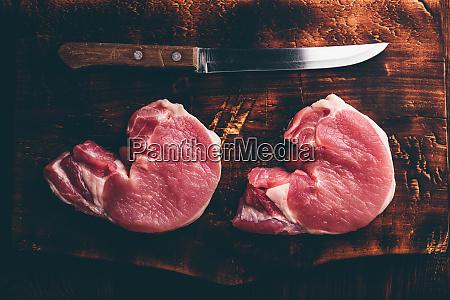 zwei schweinelendesteaks mit messer