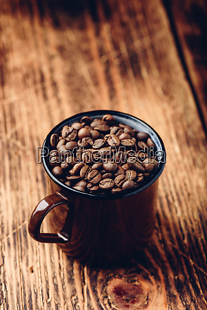 becher voller geroesteter kaffeebohnen