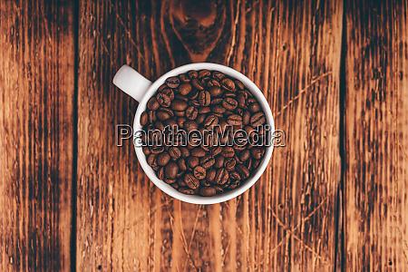 geroestete kaffeebohnen in weisser tasse