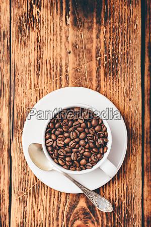 geroestete kaffeebohnen in der tasse
