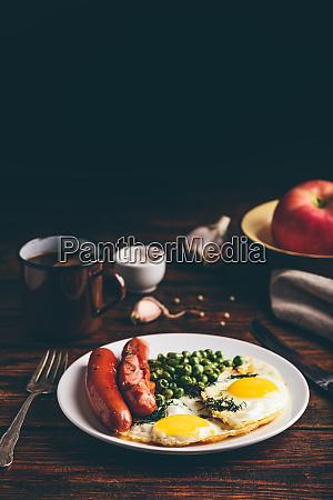 fruehstueck mit spiegeleiern wuerstchen und gruenen