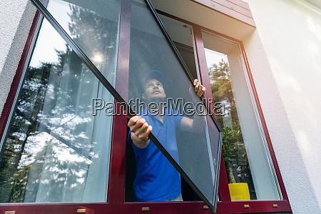 worker installing mosquito net wire screen