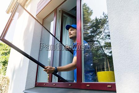 handyman installing mosquito net mesh screen