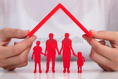 geschaeftsfrau schuetzt familienfiguren mit dach