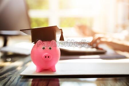 nahaufnahme von piggybank mit graduierung cap